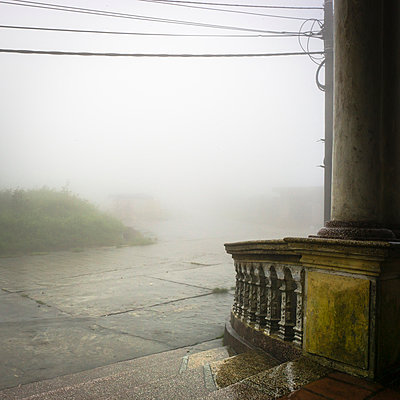 Eerie scene into the mist from the terrace of an old building - p934m1022249 by Sebastien Loffler