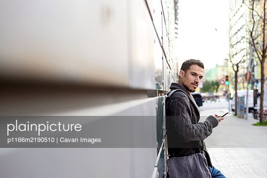 Side view of a bearded man using phone leaning on office building wall - p1166m2190510 by Cavan Images