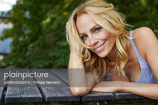Portrait of smiling blond woman lying on wooden jetty - p300m2062215 by Philipp Nemenz