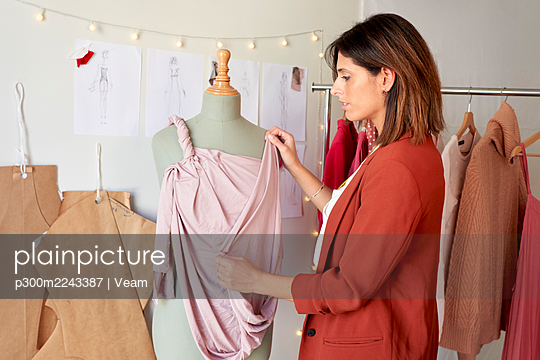 Beautiful fashion designer dressing mannequin at atelier - p300m2243387 by Veam