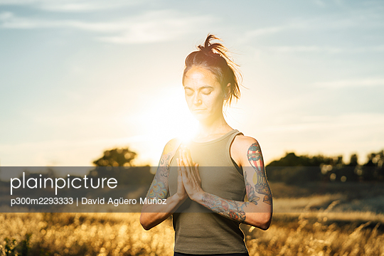 Mid adult woman meditating while doing yoga at countryside - p300m2293333 by David Agüero Muñoz