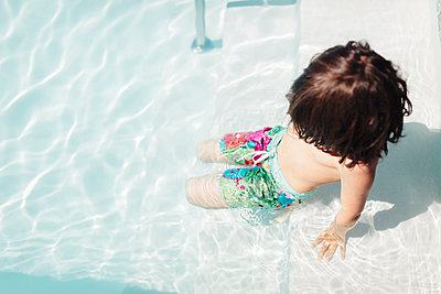 High angle view of shirtless boy playing in swimming pool during sunny day - p1166m1485256 by Cavan Images