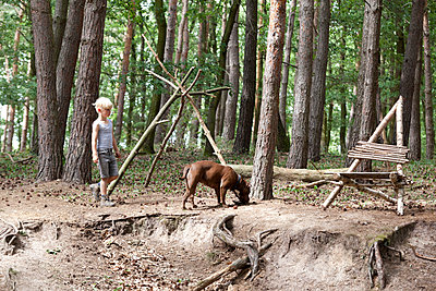 Boy walking with dog in forest - p300m1499298 by Michelle Fraikin
