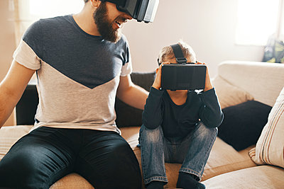 Father and little son wearing virtual reality glasses at home - p300m1581378 by Zeljko Dangubic