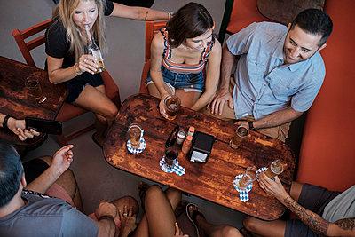 Friends socializing in a bar - p300m2078596 by André Babiak
