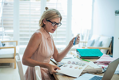 Woman with laptop working on fashion designs on table - p300m2139640 by LOUIS CHRISTIAN