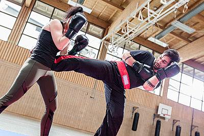 Female kickboxer sparring with coach in sports hall - p300m2144777 von Stefanie Baum