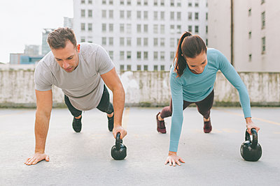 Man and woman doing push ups in the city, Vancouver, Canada - p300m2170502 by Crystal Sing