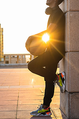 Sun shining through young man holding basketball while standing by wall at sunset - p300m2243998 by NOVELLIMAGE