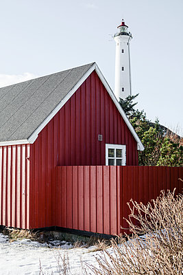 Red framehouse against white lighthouse - p327m1216585 by René Reichelt