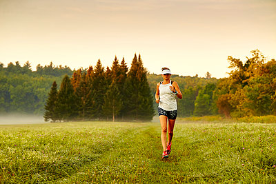 A woman running through a field on a foggy morning.  - p343m1203834 by Josh Campbell