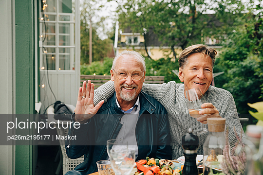 Happy male friends sitting at dining table enjoying dinner party in back yard - p426m2195177 by Maskot