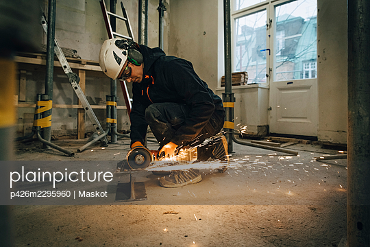 Full length of male construction worker using electric saw while cutting metal at site - p426m2295960 by Maskot