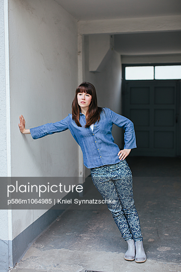 Young woman leaning against wall - p586m1064985 by Kniel Synnatzschke