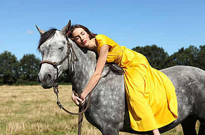Woman in yellow dress on a horse - p045m721129 by Jasmin Sander