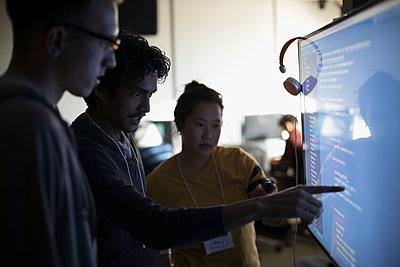 Hacker team discussing coding on computer monitor at hackathon in dark office - p1192m1202103 by Hero Images