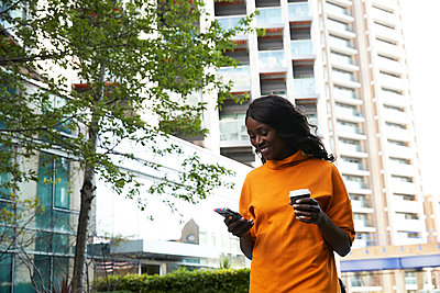 Happy businesswoman with disposable coffee cup using smart phone at office park - p300m2241038 by Pete Muller
