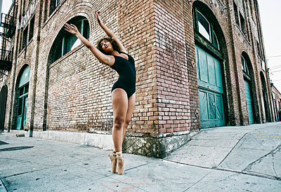 Mixed race ballet dancer on sidewalk in city - p555m1521636 by Peathegee Inc