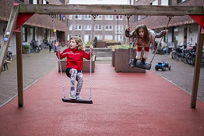 Girls playing on a swing - p896m1478955 by Amaury Miller