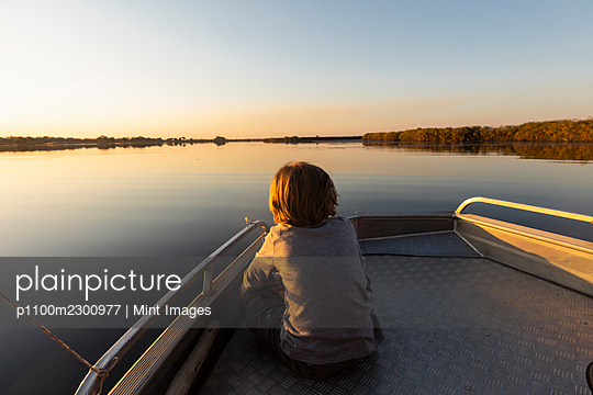 Young boy sitting at the stern of a boat on flat calm water - p1100m2300977 by Mint Images