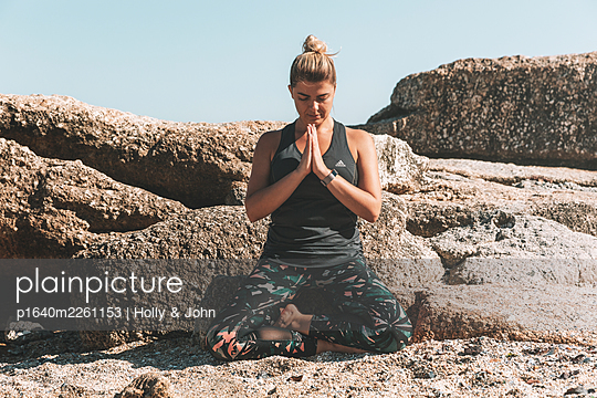 Young woman practises meditation on the beach - p1640m2261153 by Holly & John