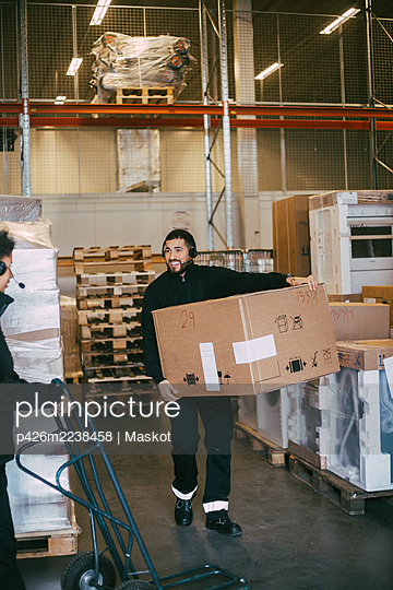 Male entrepreneur carrying box container at distribution warehouse - p426m2238458 by Maskot