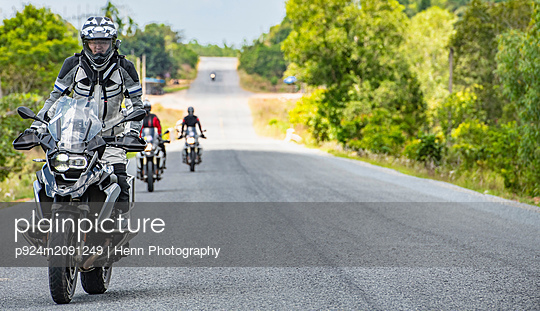 Male friends riding ADV motorcycles on rural road in Cambodia - p924m2091249 by Henn Photography