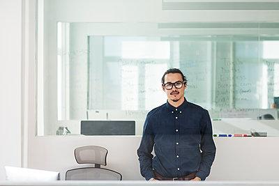Portrait of businessman standing in office seen through window - p1166m1210158 by Cavan Images