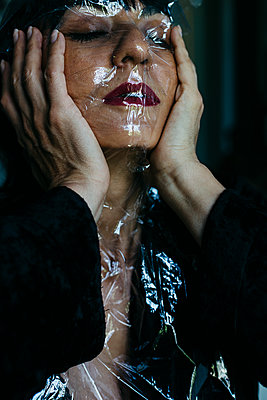 Woman with cling film wrapped around her head and face - p1621m2231952 by Anke Doerschlen