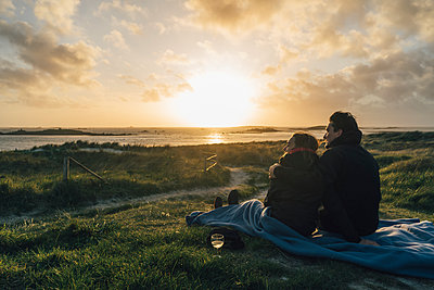 France, Brittany, Landeda, couple sitting  at the coast at sunset - p300m2004074 by Gustafsson