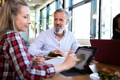 Casual business people having business lunch in a cafe - p300m2139860 by Florian Küttler