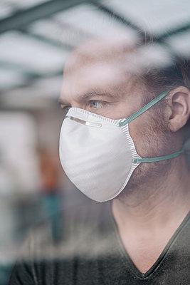 Portrait of man wearing protective mask behind windowpane - p300m2171047 by Joseffson