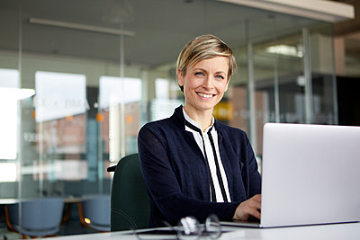 Portrait of smiling businesswoman using laptop in office - p300m2180672 by Rainer Berg
