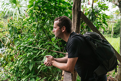 Thoughtful man with backpack leaning by railing at Misahualli, Ecuador - p300m2240220 by MORNINGVIEW AGENCY