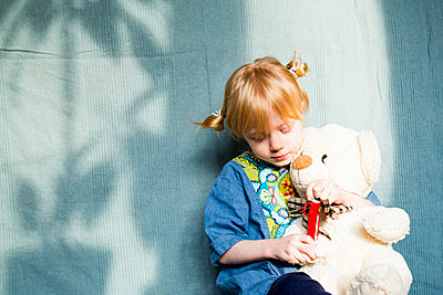 Blond girl playing with teddy bear against blue cloth during sunny day - p300m2275447 by Irina Heß