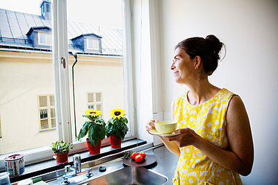 Woman drinking coffee and looking through window - p352m2119684 by Lena Katarina Johansson