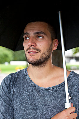 Thoughtful young man looking away while holding umbrella outdoors - p426m844791f by Fredrik Telleus