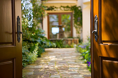Stone path leading into Spanish style courtyard - p5551534f by Blend Images