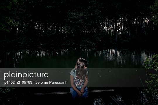 Pensive girl on a bench in the fores - p1402m2195789 by Jerome Paressant
