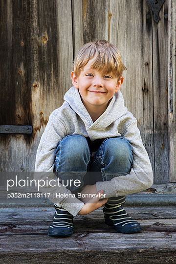 Portrait of boy crouching - p352m2119117 by Helena Bonnevier