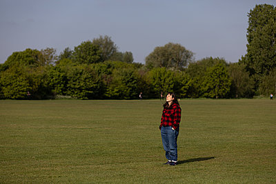 Single woman stands on lawn in a park  - p1291m2211056 by Marcus Bastel