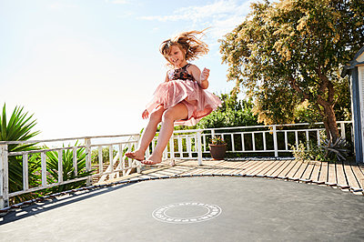 Little girl jumping on trampoline - p1640m2244893 by Holly & John
