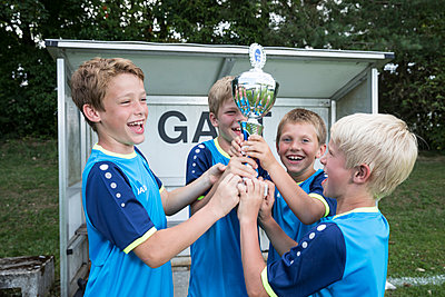 Young football players cheering with cup - p300m1581506 von Fotoagentur WESTEND61