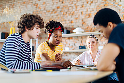 Young people sitting together at table and talking - p300m2144364 by Sofie Delauw