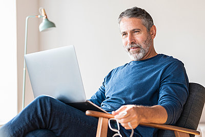 Businessman working on laptop while sitting at home - p300m2257217 by Steve Brookland