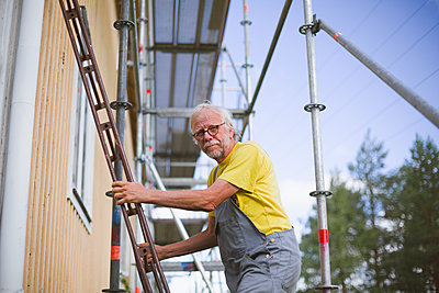 Senior man standing on ladder - p312m2162163 by Matilda Holmqvist