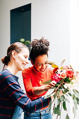 Florist and student arranging bouquet at flower arranging workshop - p429m1417601 by Alys Tomlinson