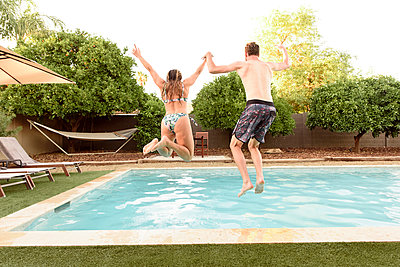 Caucasian couple holding hands jumping into swimming pool - p555m1522735 by Kolostock