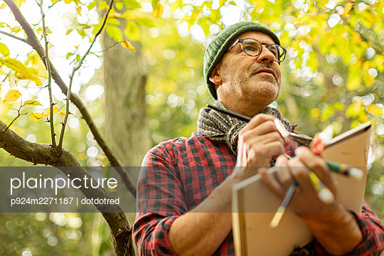 UK, London, Epping Forest, Low angle view of man painting in Autumn landscape - p924m2271187 by dotdotred