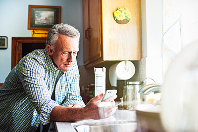 Senior man standing in a kitchen, using a mobile phone. - p1100m1177502 by Mint Images